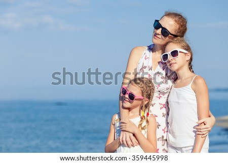 Mother and children standing on the beach at the day time. Concept of friendly family.