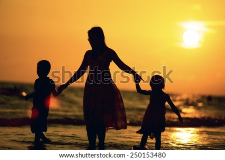 Mother and children walking along a beach on sunset - stock photo