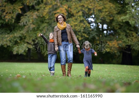 Mother and children walking in the park in autumn - stock photo
