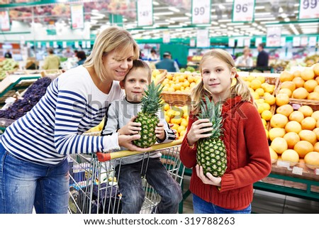 Mother and children with pineapples in fruit department in the supermarket