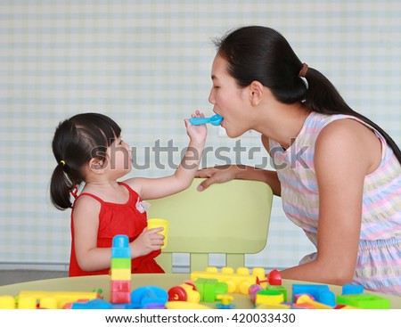 Mother and Cute asian baby girl playing block toys at the kid room