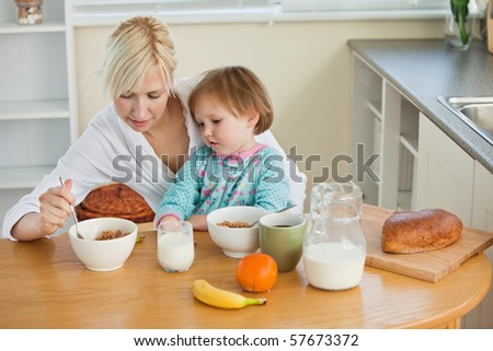 Mother and cute daughter having breakfast in the kitchen