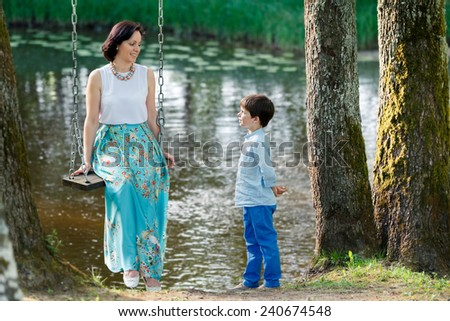 Mother and cute little boy on swing in playground outdoors - stock photo