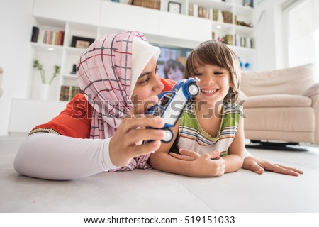 Mother and cute son playing with car toy at living room
