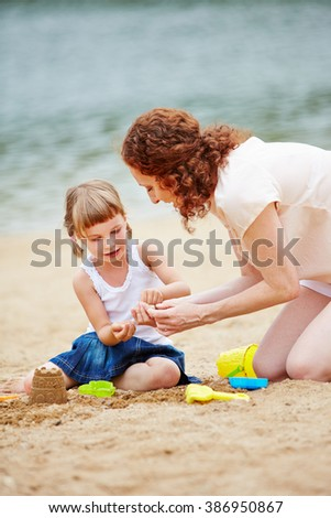 Mother and daugher playing in sand of beach and building a sandcastle