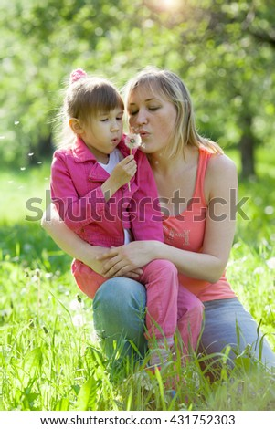 mother and daughter are blowing on white dandelion