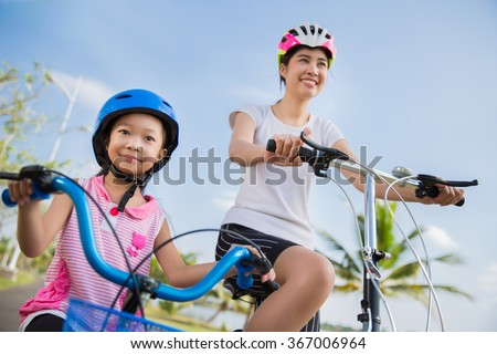 Mother and daughter are cycling exercise - stock photo