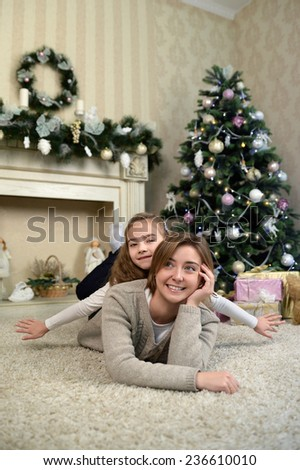 mother and daughter are dreaming near Christmas tree. Family holiday  - stock photo