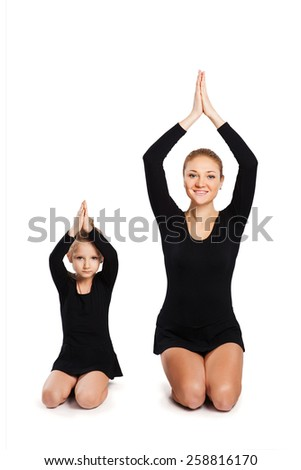 Mother and daughter are gymnastics. Practicing yoga. - stock photo