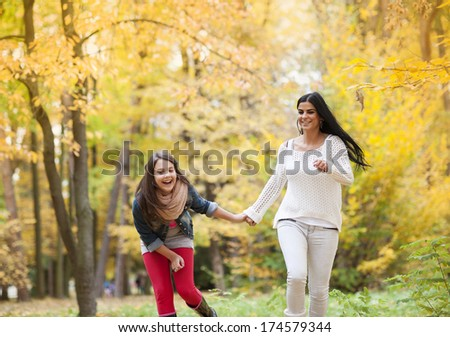 Mother and daughter are having fun in colorful autumn nature - stock photo