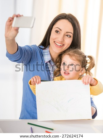 Mother and daughter are having fun while drawing at home and making a selfie photo. - stock photo