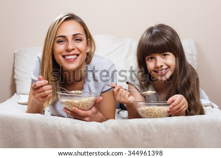 Mother and daughter are having healthy breakfast in bed.Healthy breakfast in bed for mother and daughter - stock photo