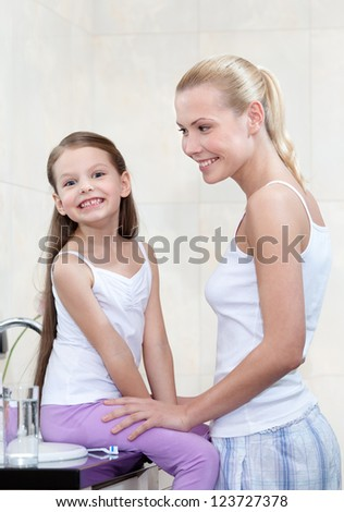 Mother and daughter are in bathroom - stock photo
