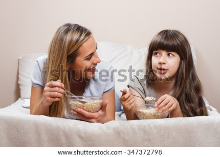 Mother and daughter are lying on bed and talking about something while they having breakfast.Mother and daughter are talking and having breakfast  - stock photo