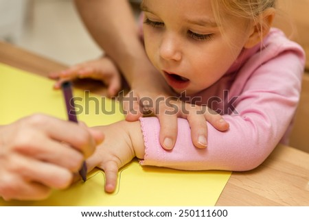 Mother and daughter are painting the Hand outline - stock photo