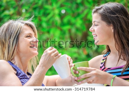 mother and daughter are relaxing at home drinking tea
