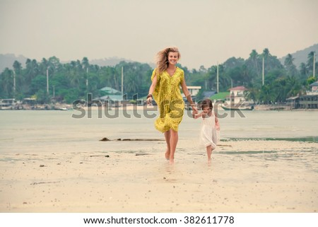 Mother and daughter are running barefoot on the tropical background.