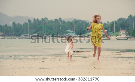 Mother and daughter are running barefoot on the tropical background. - stock photo