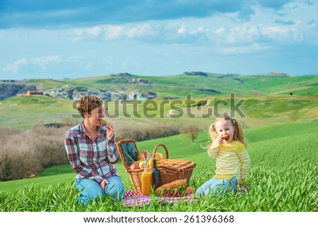Mother and daughter arranged picnic on the green spring grass in the landscape of Tuscany. - stock photo