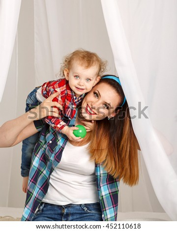 Mother and daughter at home. Young mother and baby daughter hugging and playing ball. Girls dressed in plaid shirt. Family time - stock photo
