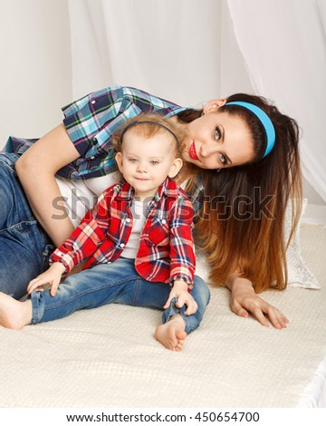 Mother and daughter at home. Young mother and baby daughter hugging. Girls dressed in plaid shirt. Daughter barefoot. Family time - stock photo