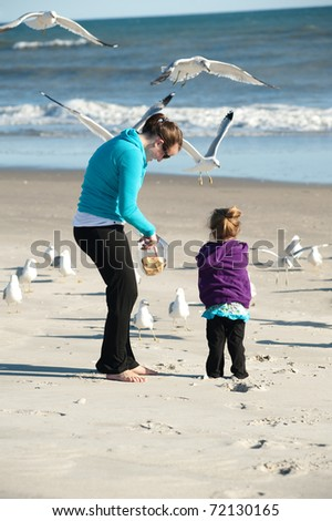 mother and daughter at the beach - stock photo