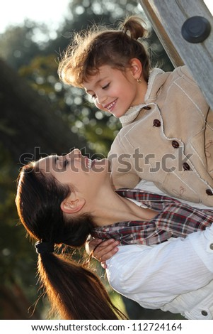 Mother and daughter at the playground - stock photo
