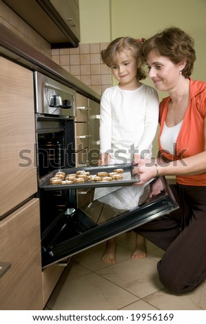 Mother and daughter baking christmas cookies - stock photo