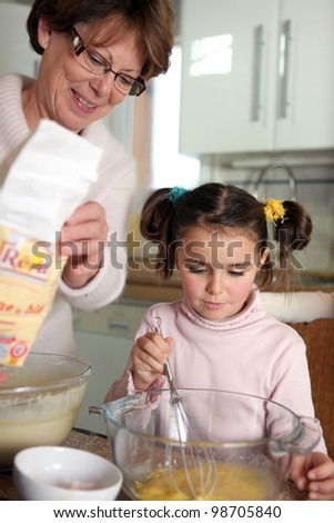 Mother and daughter baking in the kitchen - stock photo