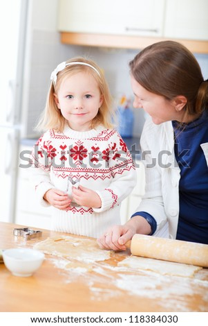 Mother and daughter baking pie or cookies at home