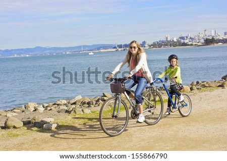 Mother and Daughter biking along the beach in San Francisco - stock photo