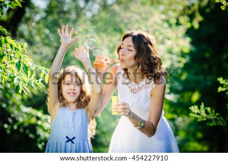 Mother and daughter blowing soap bubbles in the park - stock photo