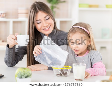 Mother and daughter breakfast in the kitchen. Cute little girl preparing cereal in the bowl. Mother drinking coffee.