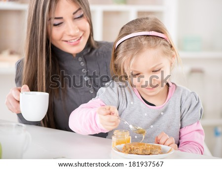 Mother and daughter breakfast in the kitchen. Cute little girl smear honey over the peanut butter on bread. Mother drinking coffee.