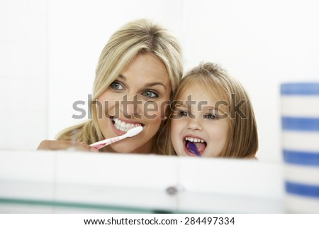 Mother And Daughter Brushing Teeth Together - stock photo