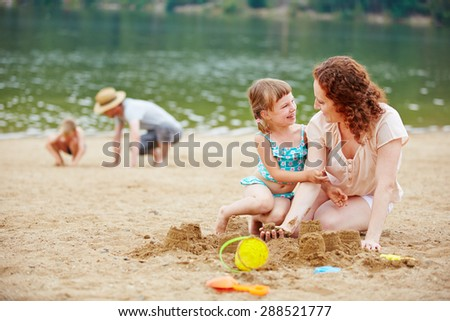 Mother and daughter building a sand castle together on a beach