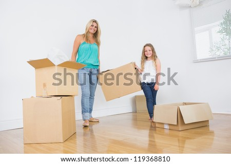 Mother and daughter carrying moving boxes in empty living room