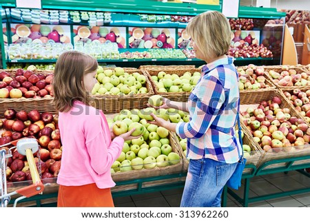 Mother and daughter chooses apples in the supermarket - stock photo