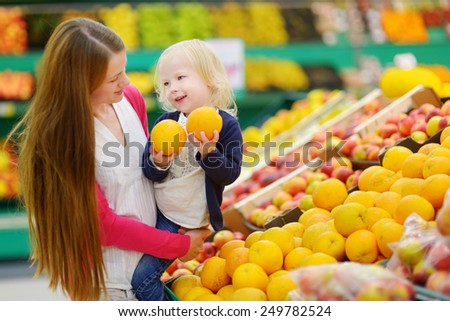 Mother and daughter choosing an orange in a fruit store
