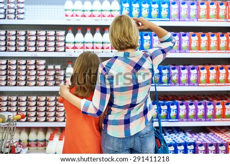 Mother and daughter choosing dairy products in shop - stock photo