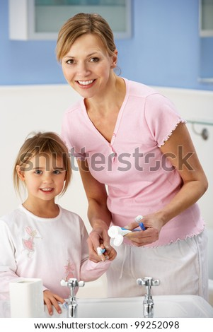 Mother and daughter cleaning teeth in bathroom - stock photo