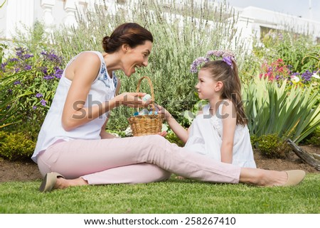 Mother and daughter collecting easter eggs outside in the garden - stock photo