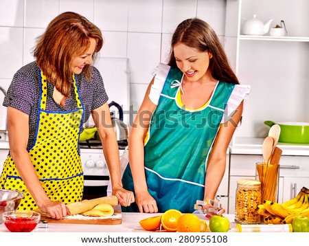 Mother and daughter cooking and talking food at kitchen. - stock photo