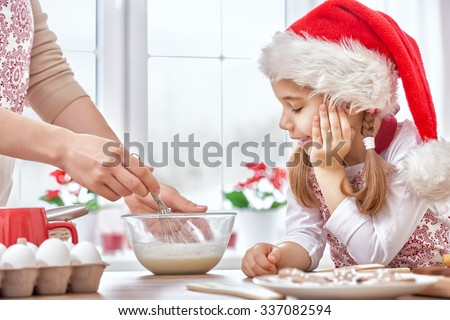 mother and daughter cooking Christmas biscuits - stock photo
