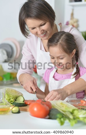 Mother and daughter cooking dinner - stock photo