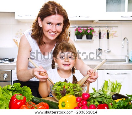 Mother and daughter cooking dinner in kitchen - stock photo
