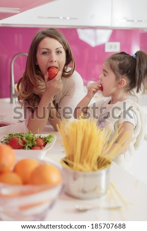 Mother and daughter cooking in the kitchen - stock photo