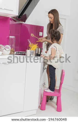 Mother and daughter cooking in the modern kitchen at home - stock photo