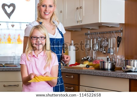 Mother and daughter cooking together, they making Lasagna - stock photo