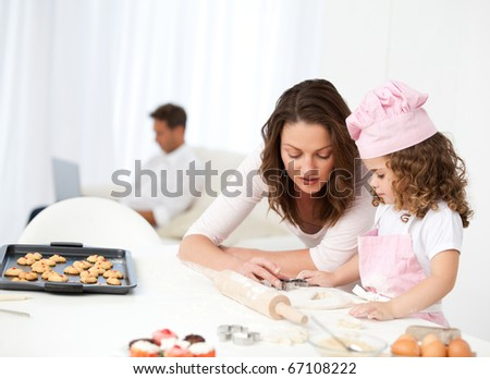 Mother and daughter cooking while dad relaxing on the sofa - stock photo